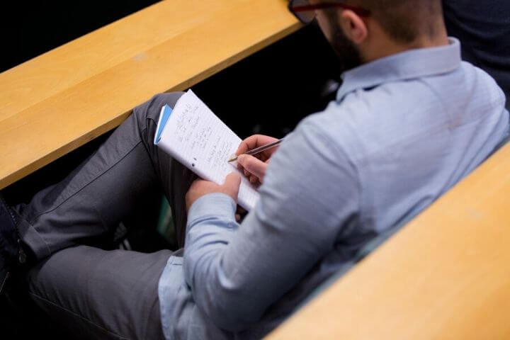 University of Sunderland in London student taking notes in a lecture