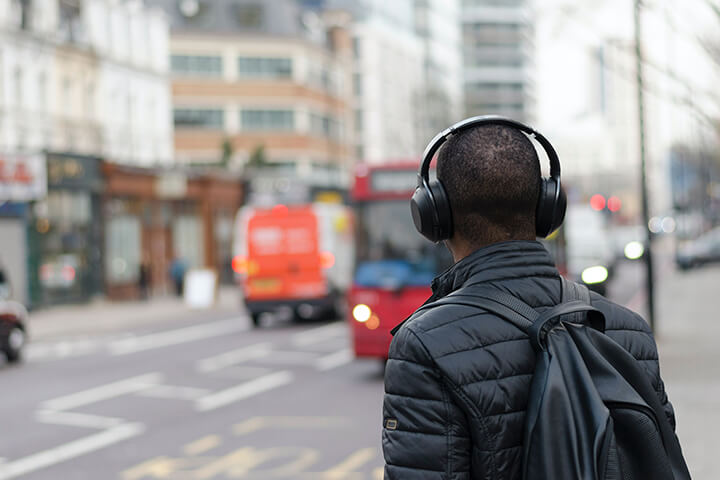 University of Sunderland in London student outside in London listening to a podcast