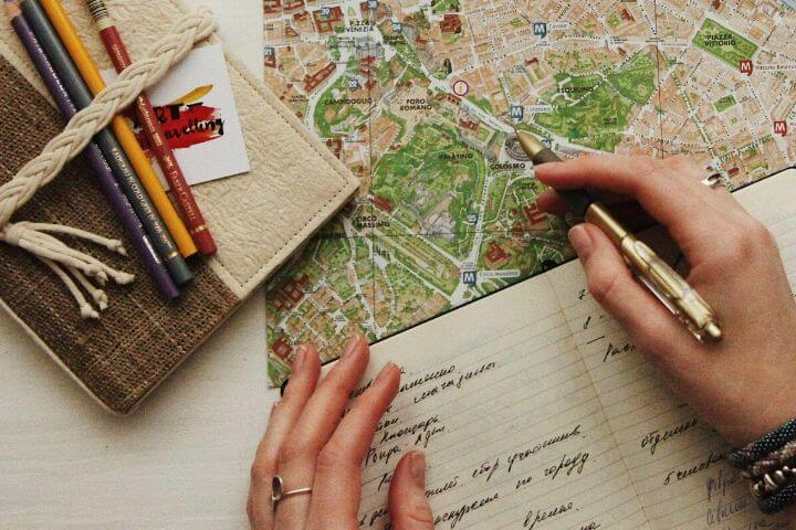 A person writing in a notebook with a map