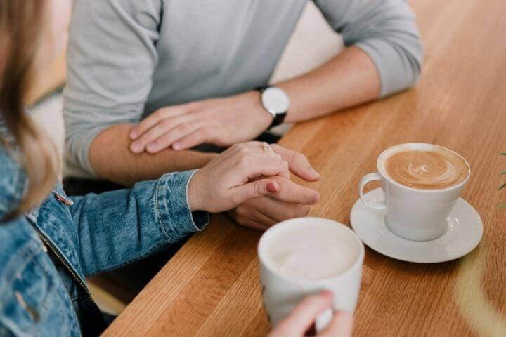 Two people talking with hot drinks