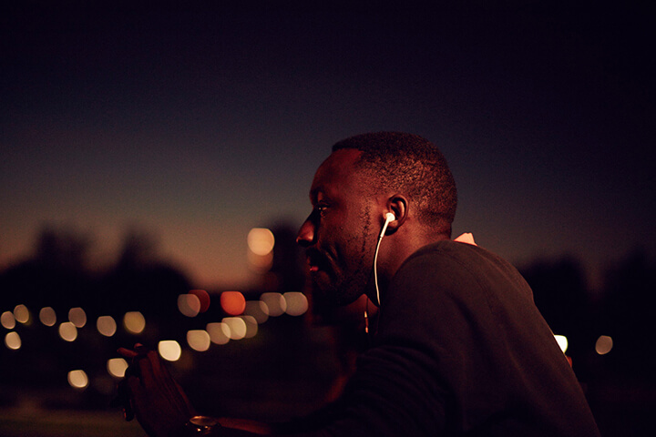 University of Sunderland in London student listening to music with earphones outside at night