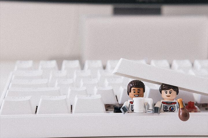 Two LEGO people inside a keyboard