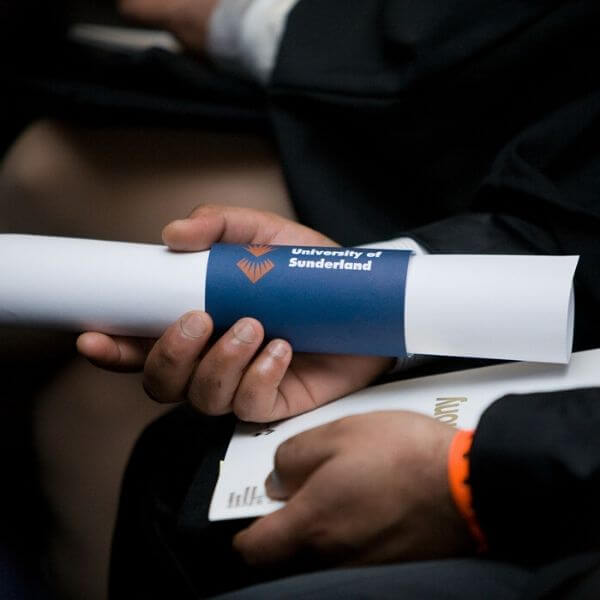 A University of Sunderland in London student at their graduation holding their certificate