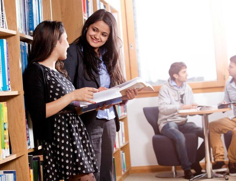 University of Sunderland in London students talking in the Library