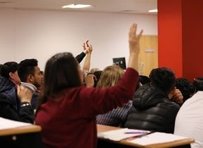 University of Sunderland in London students in a lecture room raising their hands