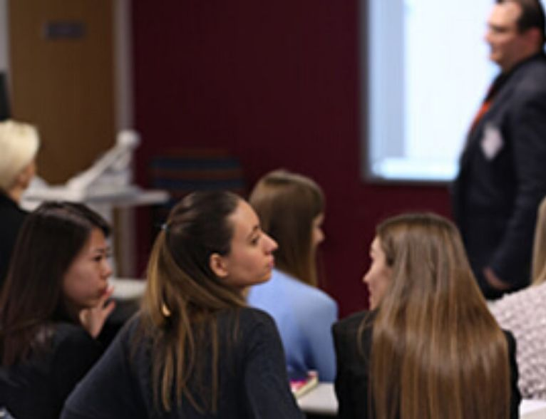 University of Sunderland in London students in a lecture room listening to a lecturer