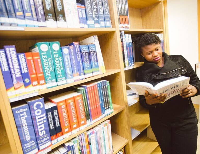 University of Sunderland in London student reading in the Library